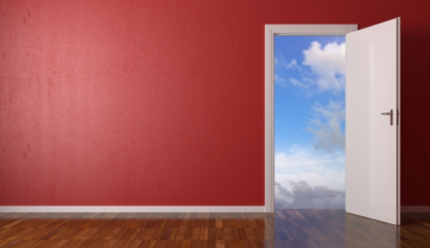 Door set in a red wall open to show the sky outside