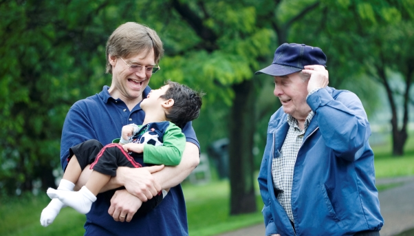 Three generations interacting together. Father holding disabled son in arms.