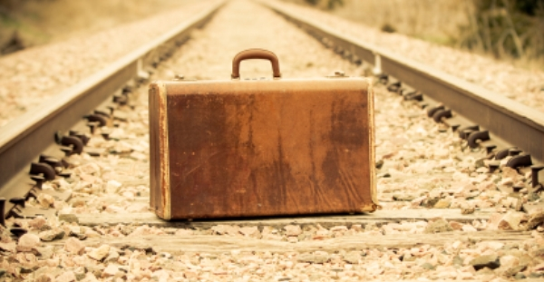 Old suitcase sitting on rail road tracks