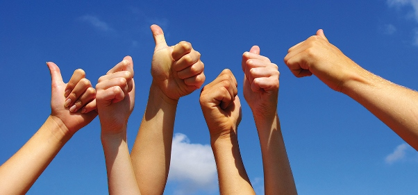 Hands in the air against a blue sky, with thumbs up
