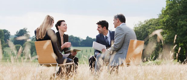 Business women and men talking in a field