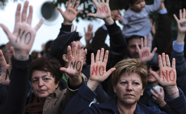 "Cypriot demonstrators showing their palms reading ""No"" during a protest against an EU bailout deal outside the parliament in the capital, Nicosia, on March 18, 2013."