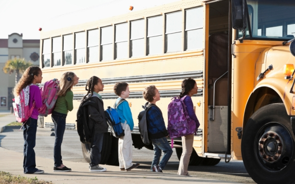 6 children waiting to get on a yellow school bus